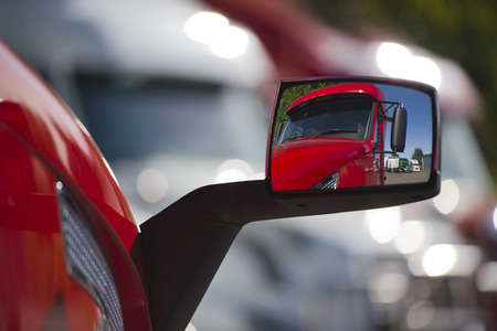 Original reflection of the contemporary red semi truck in his own rear-view mirror, as well as displaying a number of other trucks parked at the site on a background of blurred lights glare oncoming light