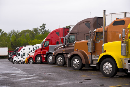 Cabins of multicolored semi trucks lined up on the truck stop after a rain with puddles on the pavement on the background of green trees and gray rainy overcast sky