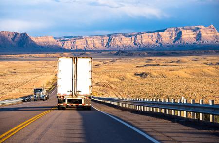 Camiones semi con furgoneta y cama plana remolques secos transportar carga en la carretera con vallas de seguridad en Utah en las sierras el sol que ilumina y colinas bajas amarillas