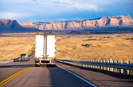 Semi trucks with dry van and flat bed trailers carrying cargo on the highway with security fencing in Utah in the sun-lit mountain ranges and yellow lowland hills