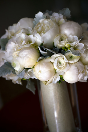 Wedding bouquet of small and large white peonies, leaves and berries in a glass vase on a dark background