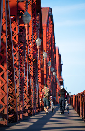 sectioned: Guy and a girl walk along the footpath sectioned red iron bridge with lanterns and railings, in perspective  Couple leads beside him their bikes  On the footpath falls the shadow of the bridge structures