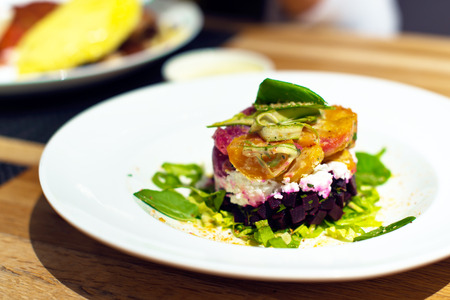 dining out: Color colorful Salad from beet, cheese, tomato, pepper and other vegetables laid out in the shape of a cylinder on a white round plate, standing on the dining room table next to the other dishes