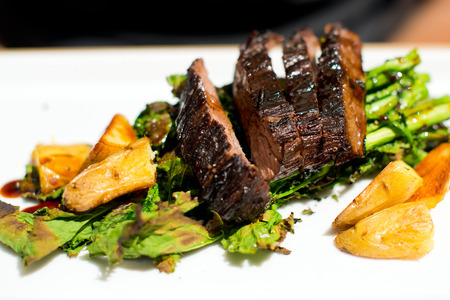 Natural organic steak beef meat cooked on the fire, and flavored seasoning of herbs and vegetables, sliced and put on a white porcelain rectangular plate  Dish grace any dining table