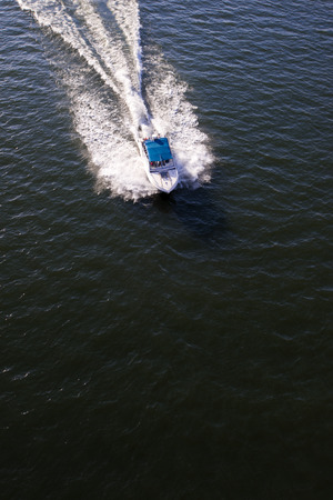 speed boat: Fast motor boat with white blue canopy rushes through the dark surface of the river, raising the waves, leaving behind a white tail foam.  Lovely active in the day