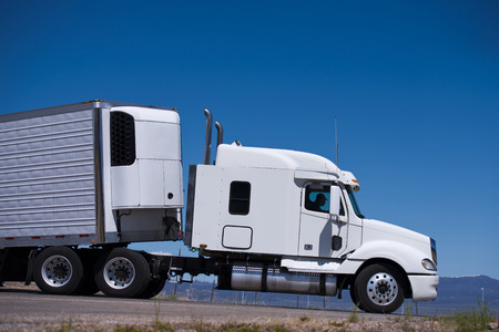 Big white truck with a trailer and a refrigeration unit on the road of the highway against the blue clear sky  Side view draws all the outlines of the modern powerful truck with chrome pipes  Stock Photo