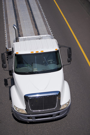 White modern middle class-duty truck for local transportation freight with flat bed trailer on the highway on a background of gray asphalt and yellow dividing line  Top view