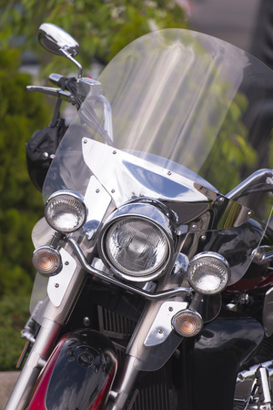 exotics: Classic motorcycle with a protective windscreen and safety helmet on the steering wheel on the background of greenery.  Front view presents us with a detailed overview of motorcycle parts and its structure
