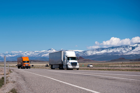 Several trucks of different colors on a straight as an arrow highway road going into perspective horizon in Utah against the backdrop of snow-capped mountain ranges, and seated on them clouds photo