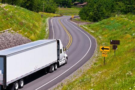 Große, moderne klassische weiße LKW mit einem Anhänger trägt kommerziellen industriellen Ladung auf dem Scenic Highway Wickeln zwischen Hügeln mit Bäumen, Gras, Blumen bedeckt und trennte die Sicherheitsbarriere mit Verkehrszeichen