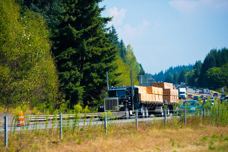 loads: Semi-Truck of classic style with large chrome pipes and bumper moves along the highway Stock Photo
