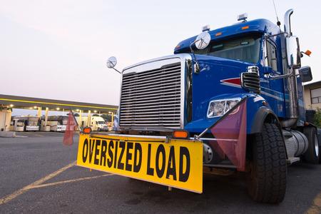 przewymiarowany: Klasyczna niebieska ciężarówka z ładunkiem ponadgabarytowych znak na postoju ciężarówki na tle stacji benzynowej z ciężarówek i autobusów. Zdjęcie Seryjne