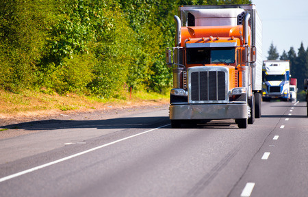 moves: Classic orange semi truck with a refrigerator on a multilane highway road ahead of a convoy of trucks with trailers moving in the right lane highway