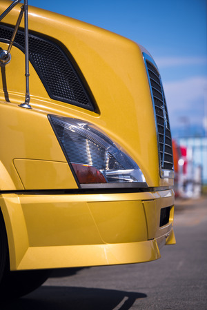 grille: Hood of a yellow semi truck with the modern grille headlamp and bumper on a blurred background of sky and asphalt.