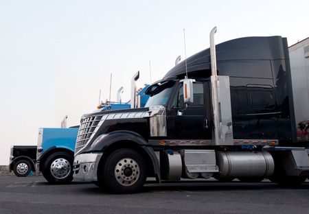 Several modern semi trucks with chrome pipes and bars in a row standing in the parking lot of truck stop waiting for the time-out on the highway
