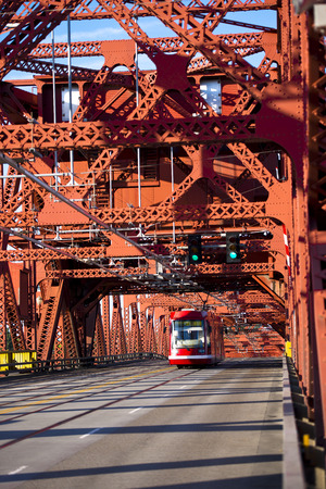 constituting: City tram on a red car and a pedestrian drawbridge metal made of riveted structures constituting the mass of triangles for strength. Editorial