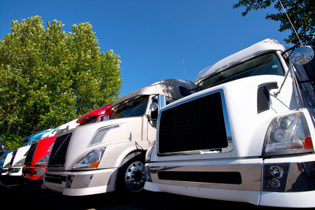 Colorful modern semi trucks lined up in a row on a truck stop and demonstrated truck hoods are made up of a grille photo