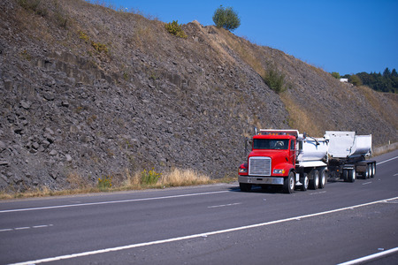 semitruck: Red semi-truck with two bulk trailers on the road on the highway against the backdrop of granite hills bulk.