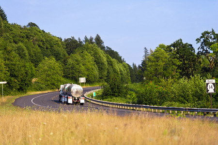 guardrails: Semi Truck carrying two stainless steel tanks with a liquid load along a winding road with safety guardrails on a background Stock Photo