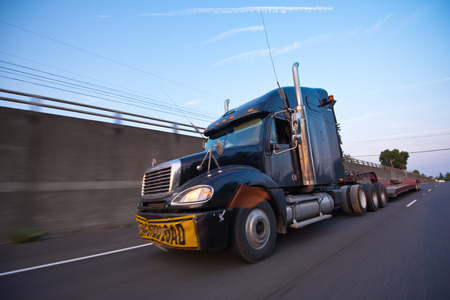 Powerful and effective modern black truck with chrome pipes and large size sign oversized load on yellow  photo