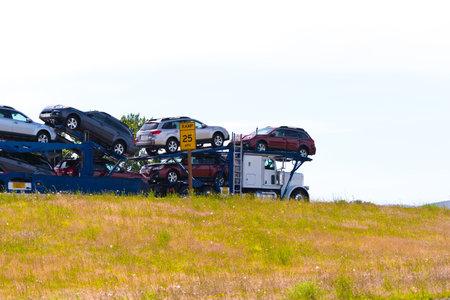 다른 색상의 자동차를 수송하고 도로를 따라 움직이는 운송 차량을위한 트레일러가 달린 훌륭한 클래식 세미 트럭 에디토리얼
