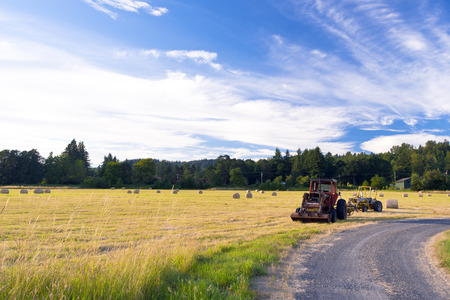 Two tractors at the edge of the field and a country earth road after work cutting grass