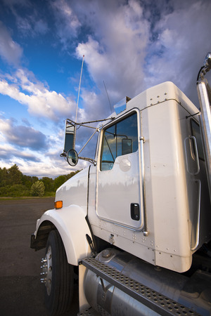 Cab of white semi truck with an aluminum tank and footrest in the future against the backdrop of spectacular clouds in the blue sky and the strip of greenery.  photo