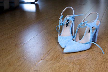 reversing: Modeling modern style elegant hip Ladies high heel shoes with pointed toes and blue ties from reversing skin on wooden floor made of bamboo with a glare of light. Stock Photo