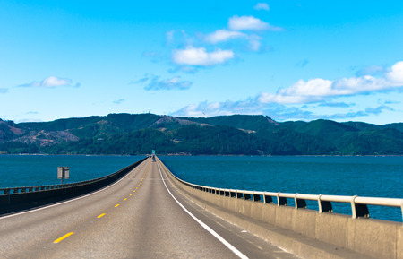 long road: Long scenic road bridge with several lanes with raised sections and fencing in wide mouth of the Columbia River in Astoria, Pacific, rests on the horizon on the opposite bank of the hilly with trees.