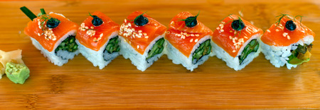 concave: Cut into equal squares role of sushi stuffed with avocado, with layers of salmon fish, olives, wasabi, wrapped in white rice. Folded diagonally in even row on a wooden rectangular bamboo plate.