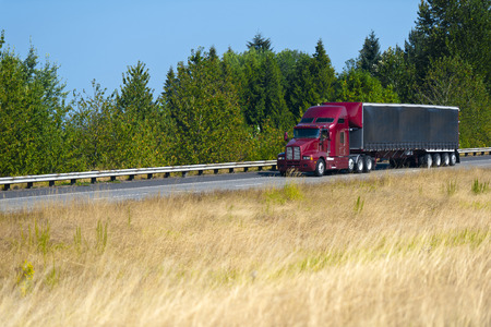 truck trailer: Red modern semi truck with a turp trailer with a spoiler over the roof on the highway on a background summer picturesque dried herbs and green wall of trees at the roadside with metal security fence. Stock Photo
