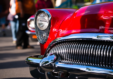 Retro Vintage red car with chrome accents headlamp grille and bumper reminiscent of the outline face predatory sharks in traditional outdoor exhibition of old cars in a small American provincial town. Archivio Fotografico