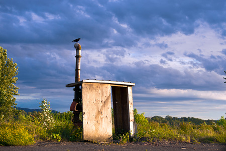 Remnants of the former building of the wooden wall with a doorway and the roof over which a metal pipe sticking out from the old communication with valve flap in the middle. Crow sitting on the tube, as a symbol of change and ending on the former prosperi