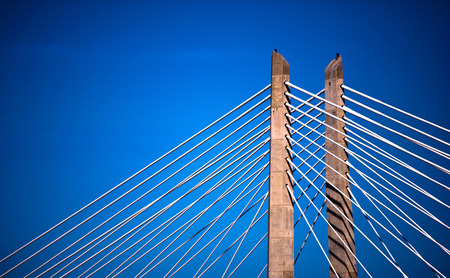 Rope suspension bridge stretching with two concrete supports columns through which the cable support structure of the bridge. Rope covered the sun on a background of blue sky saturated