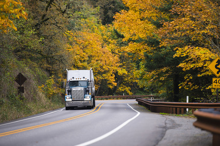 Large cool classic semi truck with chrome accents and high tailpipes and a trailer on a scenic road with twists, metal fencing and a dividing strip on the background wall of bright autumn trees. Archivio Fotografico