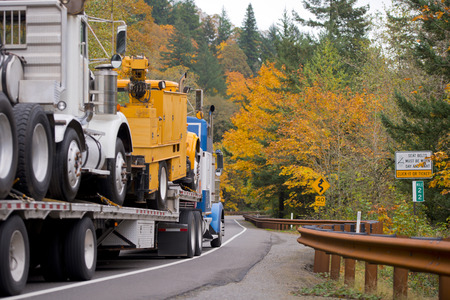 Big blue semi truck with a flat bed trailer transports other vehicles on the trailer including classic white semi truck on beautiful romantic autumn highway with metal security fence and yellow trees.