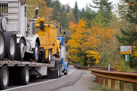 플랫 베드 트레일러와 함께 큰 파란색 세미 트럭 금속 보안 울타리와 노란색 나무와 아름 다운 로맨틱 가을 고속도로에서 클래식 화이트 세미 트럭을