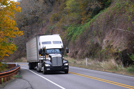 Large modern black-and-white classic bonneted semi truck with refrigerated trailer on the picturesque hilly road, metal fencing and a dividing strip on the background of yellow and dried autumn trees.