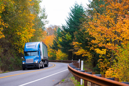 Big rig blue bonnet classic semi-truck with a bulk trailer in the picturesque winding road, metal fencing and a dividing strip on yellow background colorful autumn trees in Columbia Gorge. Archivio Fotografico