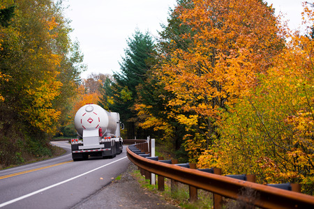 liquefied: Great classic truck with tanker trailer for the transport of liquefied natural gas at the turn of the winding road with a metal fence and a dividing strip on yellow background colorful autumn trees