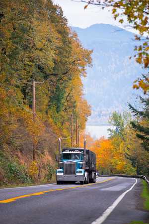 scenic highway: Large classic blue semi truck with tarp covered trailer climbing uphill on a scenic highway with metal security fence and road markings surrounded by yellow autumn trees on both sides of the road on the background of the river and mountains