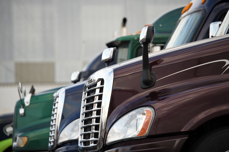 horizontal line: Chrome grille and headlights stylish and modern mirrors and hood with glass booths modern semi trucks of different coulors lined up on a platform truck stop against the gray walls of the building