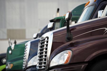 horizontal lines: Parrilla cromada y los faros de estilo y espejos modernos y capucha con cabinas de cristal semi camiones modernos de diferentes coulors alineados en una parada de camiones plataforma contra las paredes grises del edificio