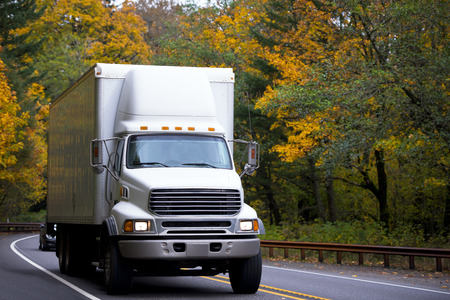White semi truck middle class with a spoiler on the cab roof and white box body moving on a winding autumn forest highway carries a variety of loads, as a link between producers and consumers. Stock Photo