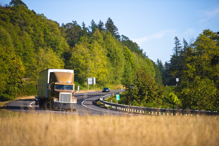 cornering: Large spectacular classic bonnet brown truck with trailer cornering scenic winding road in Columbia Gorge on a background of green trees and grass yellowed autumn