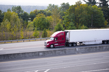 Modern expressive spectacular heavy semi trucks with aerodynamic bodywork and refrigerated trailer with spoilers on the highway with a concrete separation barrier and the markings on the background of green trees.