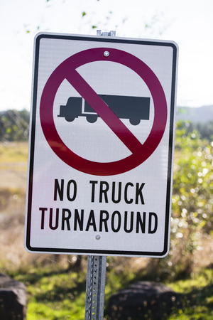 Prohibiting traffic sign on a white background which shows a truck in the red circle crossed a red stripe with the words under the picture reversal semi trucks is prohibited against a blurred background of green spaces