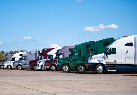 Semi trucks of different brands of classical and modern styles and different colors lined up in a straight line in a row on the tarmac truck stop waiting for the next restart and start working driving cycle.