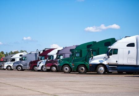 Semi vrachtwagens van verschillende merken van de klassieke en moderne stijlen en verschillende kleuren opgesteld in een rechte lijn in een rij op de tarmac truck stop te wachten op de volgende herstart en begint te werken rijcyclus.
