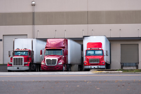 pier: Three red semi truck manufacturers and various modifications from the classic old models to modern aerodynamic semi trucks with dry van trailers are standing side by side in one line under the docks warehouse for loading or unloading.